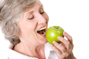 older woman with dental implants eating an apple